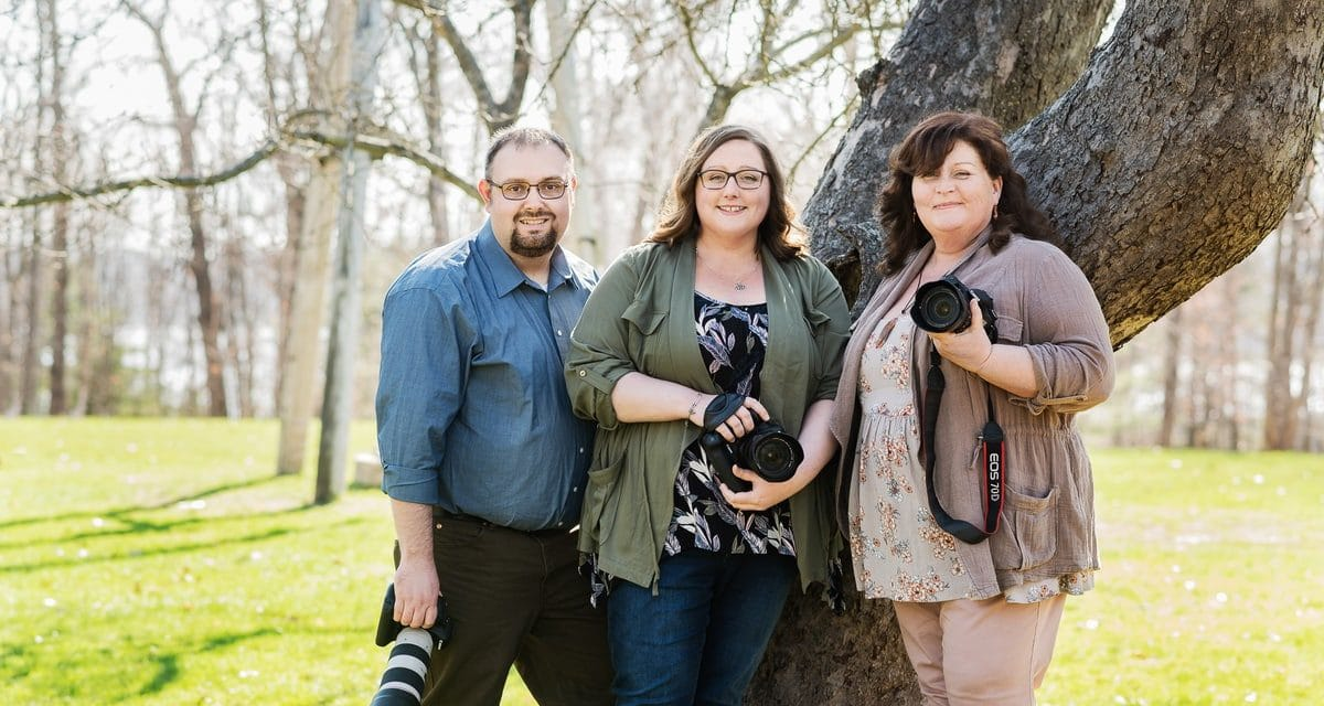 Flutter Focus Photography Team by Wohler & Co Emily, Joanne, and Allen Posing next to a tree with Cameras